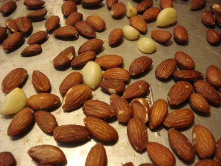 Toss some almonds and a few cloves of garlic with a tablespoon or so of olive oil, spread then out on a baking sheet and leave them in a 400 degree oven for 10 minutes.