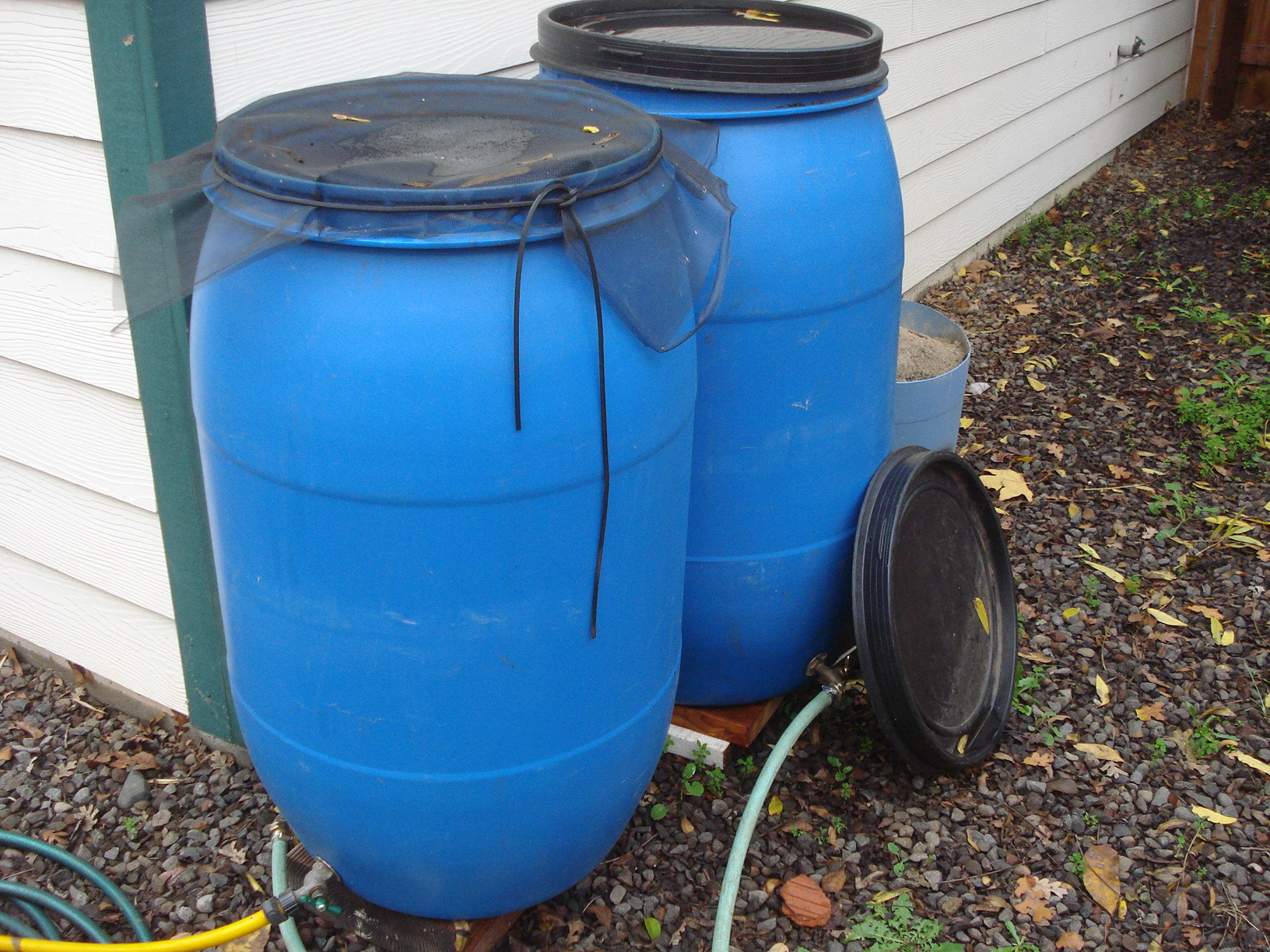 a longer rain gutter requires two barrels behind the house - Water Storage Barrels